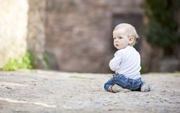 Little boy crawling on stone paved sidewalk Stock Image