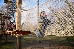 Little boy crawling on suspension net bridge. horizontal Stock Photos