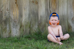 Little Boy is Crying Alone in the Grass. The Child Cries Outdoors. Copy Space Stock Photo