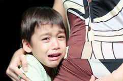 Little boy crying holding his mother black background Stock Images