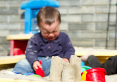 A little boy crying in the sandbox. Blurred focus Stock Image