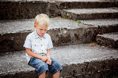 Little Boy crying  sitting on stone steps in park. Loneliness, m Stock Image