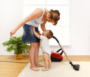 Little boy crying to be picked up. Mother cleaning the floor while she's baby is crying and wants to be picked up Stock Images