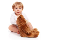 Little boy cuddling with his teddy bear Stock Photos