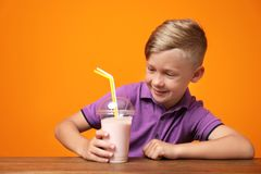 Little boy with cup of milk shake at table. On color background stock image