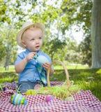 Little Boy curioso que juega con los huevos de Pascua afuera en parque Fotografía de archivo libre de regalías