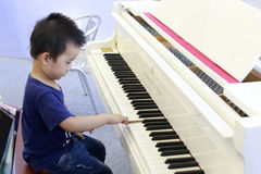 The little boy curiously press the piano key Royalty Free Stock Photography