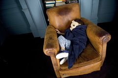 Little boy curled up asleep in armchair Stock Images
