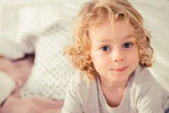 Little boy with curly hair. Little boy with blonde curly hair sitting on the bed Stock Image