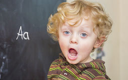 Little boy with curly hair at the old black school board Royalty Free Stock Image