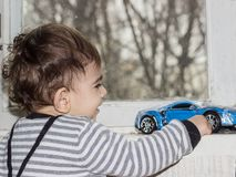 The kid plays with a toy car . Emotional portrait of a one-year-old child. royalty free stock images