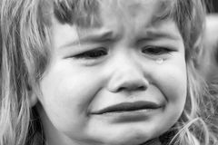 Little boy cries with tears. Little boy with cute emotional face and blond long hair cries with tears outdoor Stock Photography