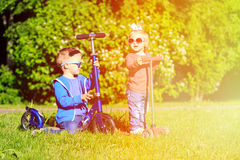 Little boy and cute girl riding scooters in park Royalty Free Stock Image