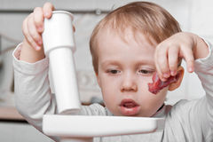 Little boy cutting meat Stock Image
