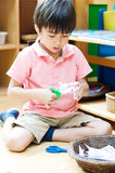 Little boy cutting paper of montessori educational Stock Photography