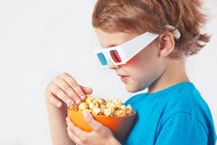 Little boy in 3D glasses with bowl of popcorn Royalty Free Stock Photo