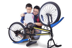 Little boy and dad fixing bicycle Stock Image