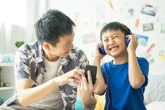 Little boy with dad listening to music on bed in bedroom stock photo