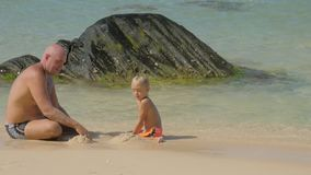 Little boy and daddy play with clean wet sand on surf line