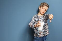Little boy with dairy allergy holding glass of milk. On color background Stock Photography