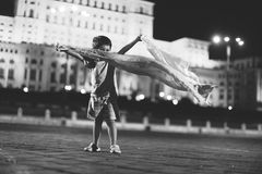 Little boy dancing in the night city view. Toddler dancing in front of the Palace of Parliament Bucharest, Romania, night scene Royalty Free Stock Photography