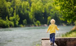 Little boy in dangerous situation during walk in park. Child safety concept. Child goes near the cliff royalty free stock photo