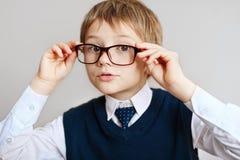 Little Boy dans des lunettes dans un uniforme scolaire blanc de chemise, de lien et de gilet Le sourire gai ouvre sa bouche dans  Photographie stock