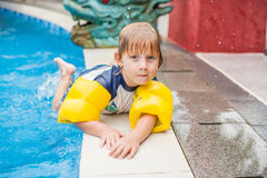 LITTLE BOY DANS LA PISCINE ET LE SOURIRE Photo stock