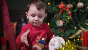Little boy with dark hair, wearing a red sweater, deer playing with yellow shiny Christmas garland, he knocks on her his stock video footage