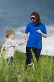 Little boy is daryl pregnant mother field flowers Royalty Free Stock Photo