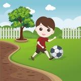 Little Boy, das Ball auf dem Rasen spielt Stockfotos