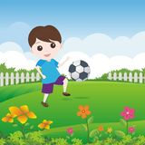 Little Boy, das Ball auf dem Rasen spielt Stockfotografie