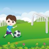 Little Boy, das Ball auf dem Rasen spielt Lizenzfreie Stockfotos