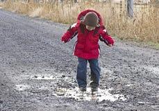 Little Boy, das in der Regen-Pfütze spielt Lizenzfreie Stockfotografie