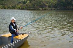 Little Boy, das ein Fischereirod and fishing from wooden-Boot auf dem See hält Lizenzfreies Stockfoto