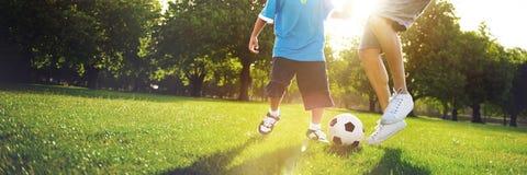 Little Boy, das Fußball mit seinem Vater Concept spielt Stockfotografie