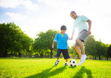 Little Boy, das Fußball mit seinem Vater spielt Lizenzfreie Stockbilder