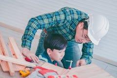 Little Boy, das lernt, an Holz zu arbeiten und ein Erbauer von seinem craftman Vater zu sein lizenzfreie stockfotos