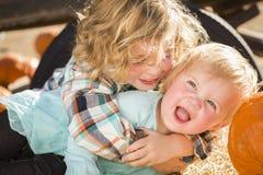 Little Boy, das mit seinem kleinen Schwesterchen am Kürbis-Flecken spielt Stockfotografie