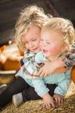 Little Boy, das mit seinem kleinen Schwesterchen am Kürbis-Flecken spielt Stockbild