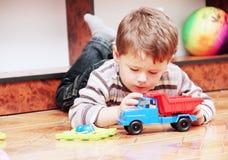Little Boy, das mit Spielzeug-Auto spielt stockfotos