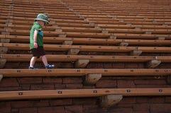 Little Boy, das am Rot geht, schaukelt Amphitheater Stockfoto