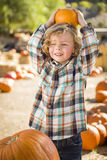 Little Boy, das seinen Kürbis an einem Kürbis-Flecken hält Stockfotos