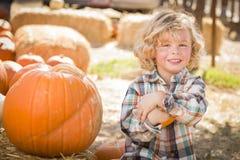Little Boy, das seinen Kürbis am Kürbis-Flecken sitzt und hält Lizenzfreie Stockfotografie