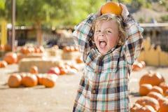Little Boy, das seinen Kürbis an einem Kürbis-Flecken hält Lizenzfreies Stockbild