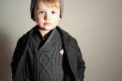 Little Boy de moda en niño rubio de Cap.Stylish Kid.Fashion Children.Handsome. Capa del invierno Style.Warm. Icono Fotografía de archivo libre de regalías