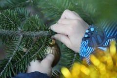 Little boy decorates christmas tree stock photo