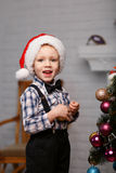 Little boy decorates a Christmas tree in the interior with Chris Stock Photo