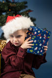 Little boy decorates the Christmas tree. Spruce with decorations. Kid and adornment. Kid and spruce with decorations and lights bokeh. Little boy and gift under stock image