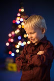 Little boy decorates the Christmas tree. Spruce with decorations. Kid and adornment. Kid and multicolor spruce with decorations and lights bokeh. Child and gifts stock photography